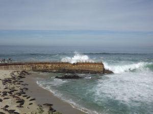 Wave crashing over end of seawall